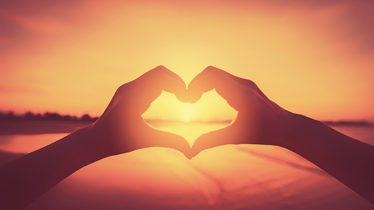 Female hands heart shape on nature bokeh sun light flare wave and blur tropical sunset beach abstract background. Copy space of happy love travel and freedom in nature concept. Vintage tone color style.